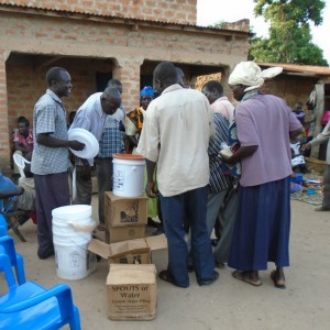 community members buy spouts of water filters
