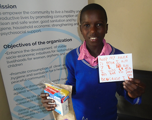 Henry, a health club member of Ogobai primay school holding his gift bag from the children in USA deliverd by SURGE Team