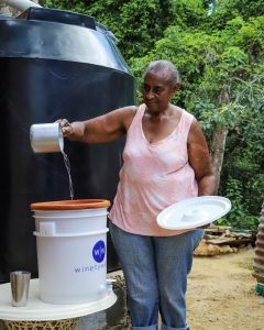 Woman pouring water into a water filter, standing in front of a rainwater tank